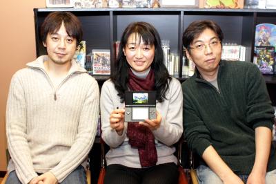 Michiko Naruke, com o compositor Hitoshi Sakimoto à esquerda e o produtor Tetsuya Okubo à direita